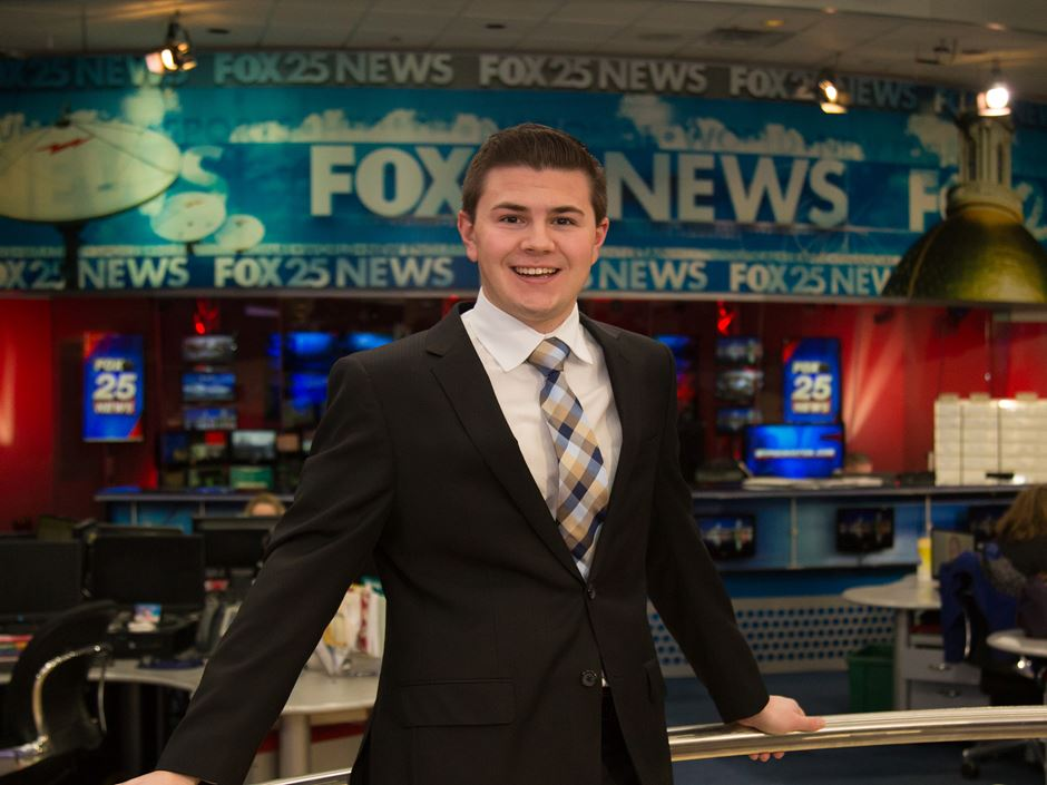 Male student pictured in front of the Fox25 newsroom while on internship.