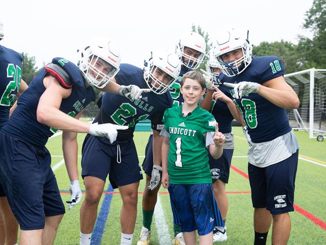 Team IMPACT participant Erik Bell poses with members of the Endicott College Football team