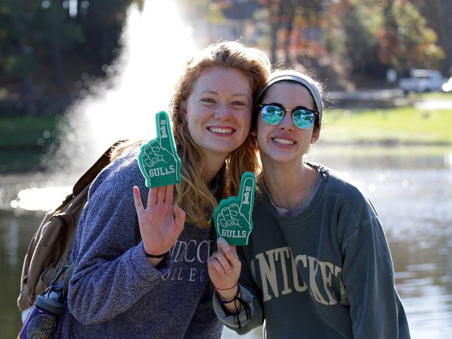 Two students holding up #1 foam fingers at last year's Homecoming and Family Weekend 2017.
