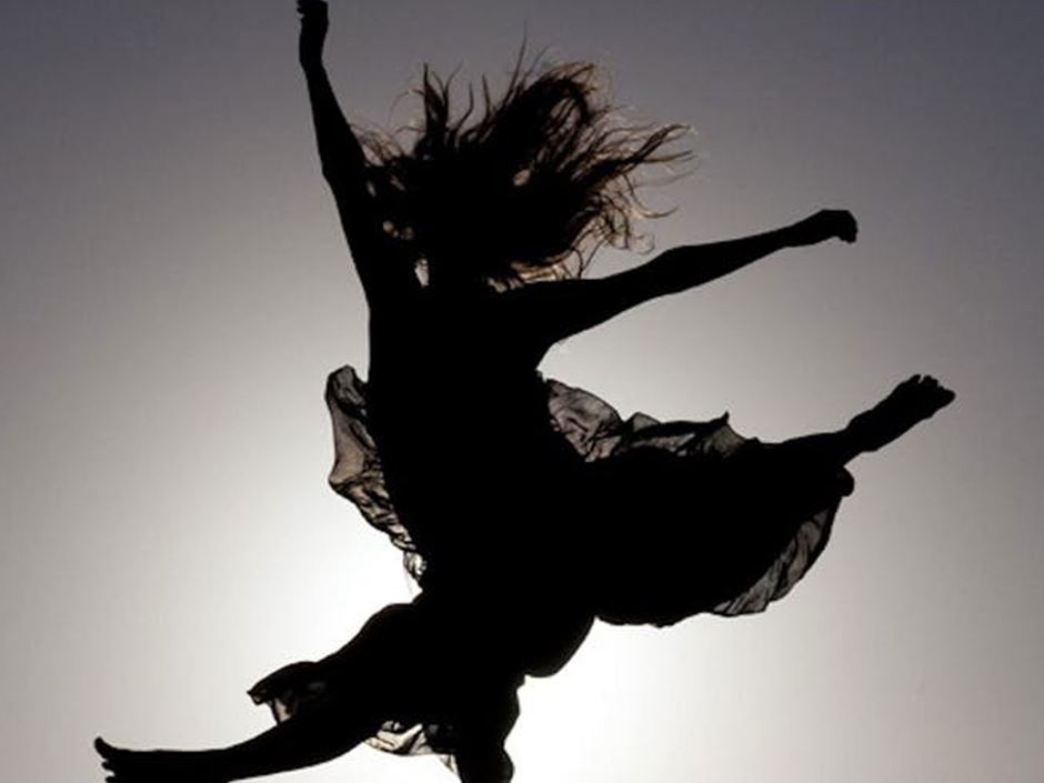 A backlit silhouette of a dancer leaping through the air
