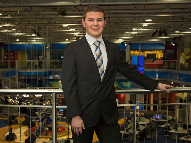 Matt Leighton posing in a newsroom