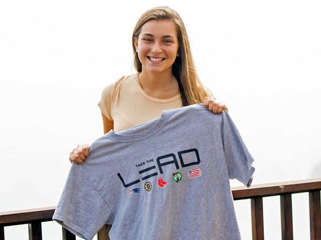 "Ella Folsom-Fraster holding a ""Take the Lead"" tee shirt"