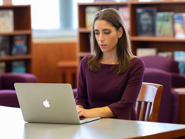 Lara Salahi working at her computer.