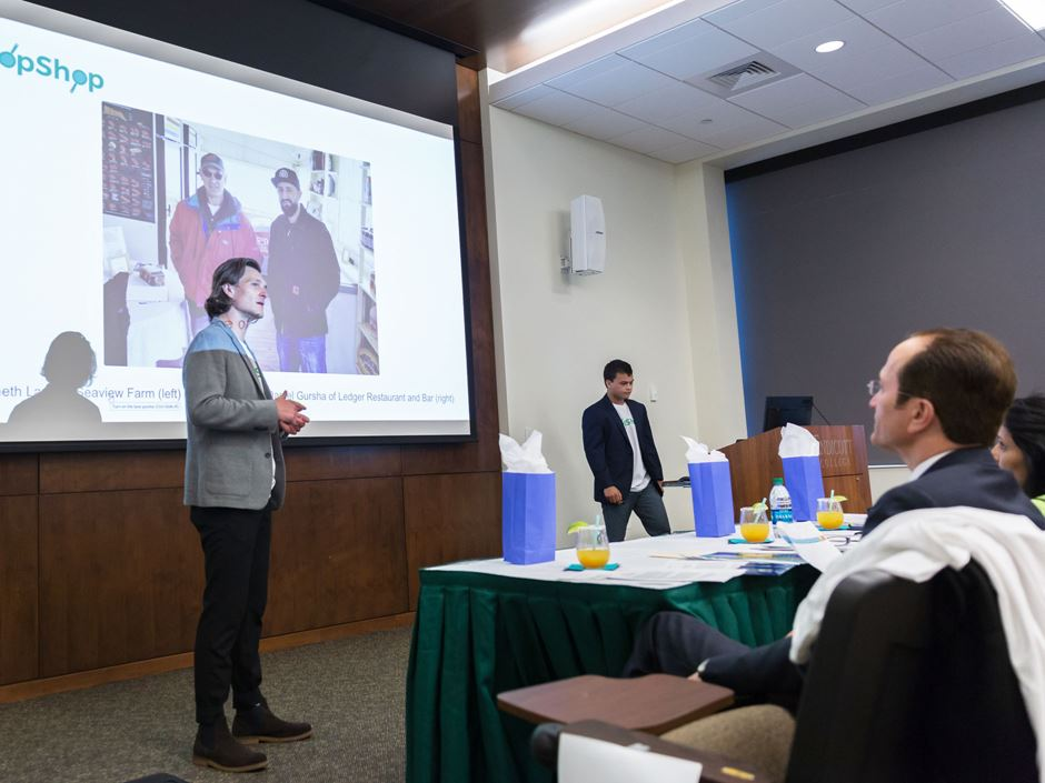 A man standing in front of a projector pitches his business idea to a panel of judges