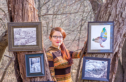 Artist Zoe Matthiessen poses with some of her work outside in the woods