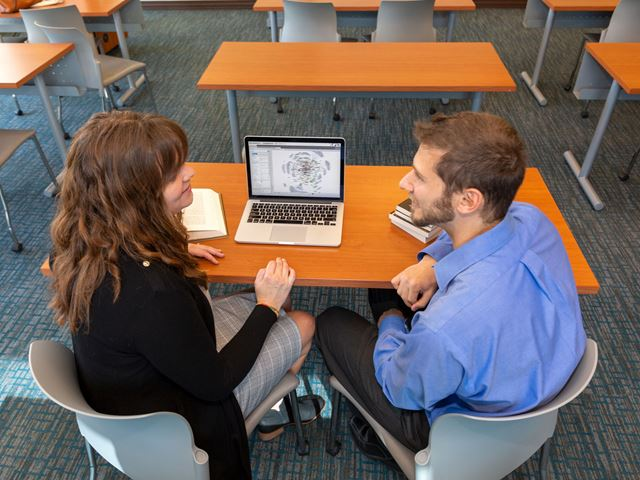 Professors Elizabeth Matelski and Philip Lombardo working at a table