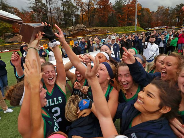 Field hockey team hoisting the CCC Championship trophy