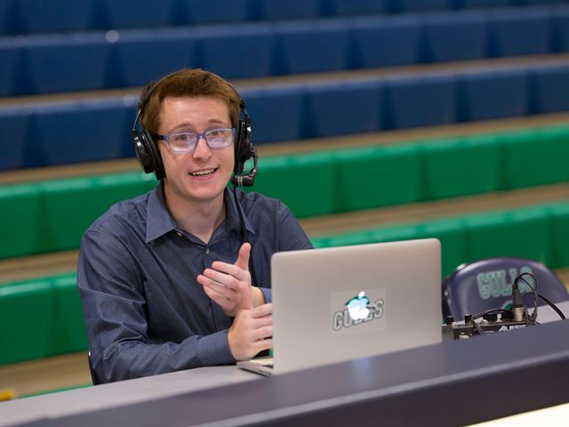 Zach Weiss '18 broadcasting at a scorer's table