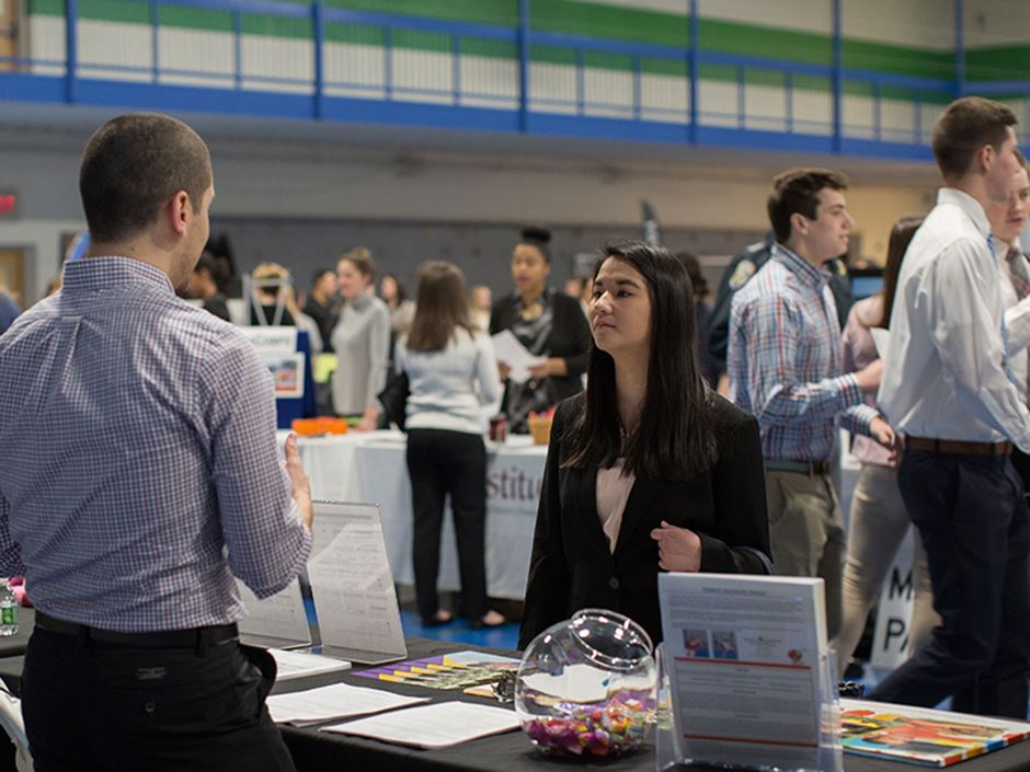 Student engaging with employers at internship fair.