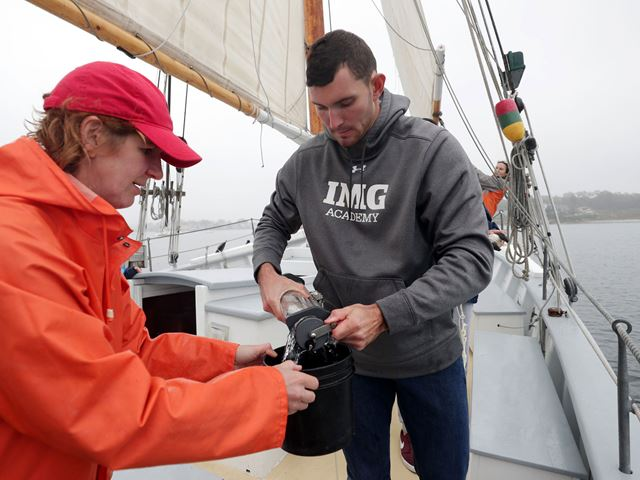 Mari Butler and student in oceanography course examine species from the ocean on a class field study trip.