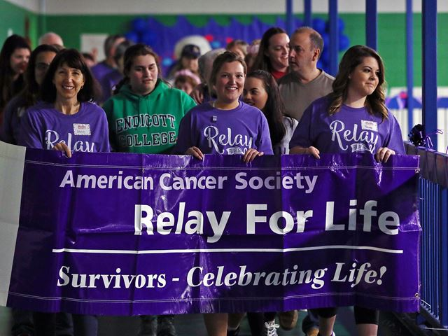 "Relay for Life participants walking with a sign that reads ""American Cancer Society, Relay for Life: Survivors—Celebrating Life!"""
