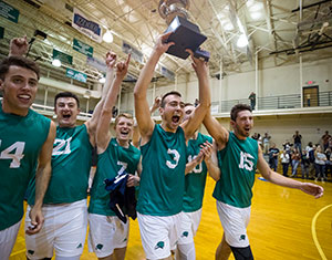 Men's volleyball student-athletes hoisting the NECC championship trophy