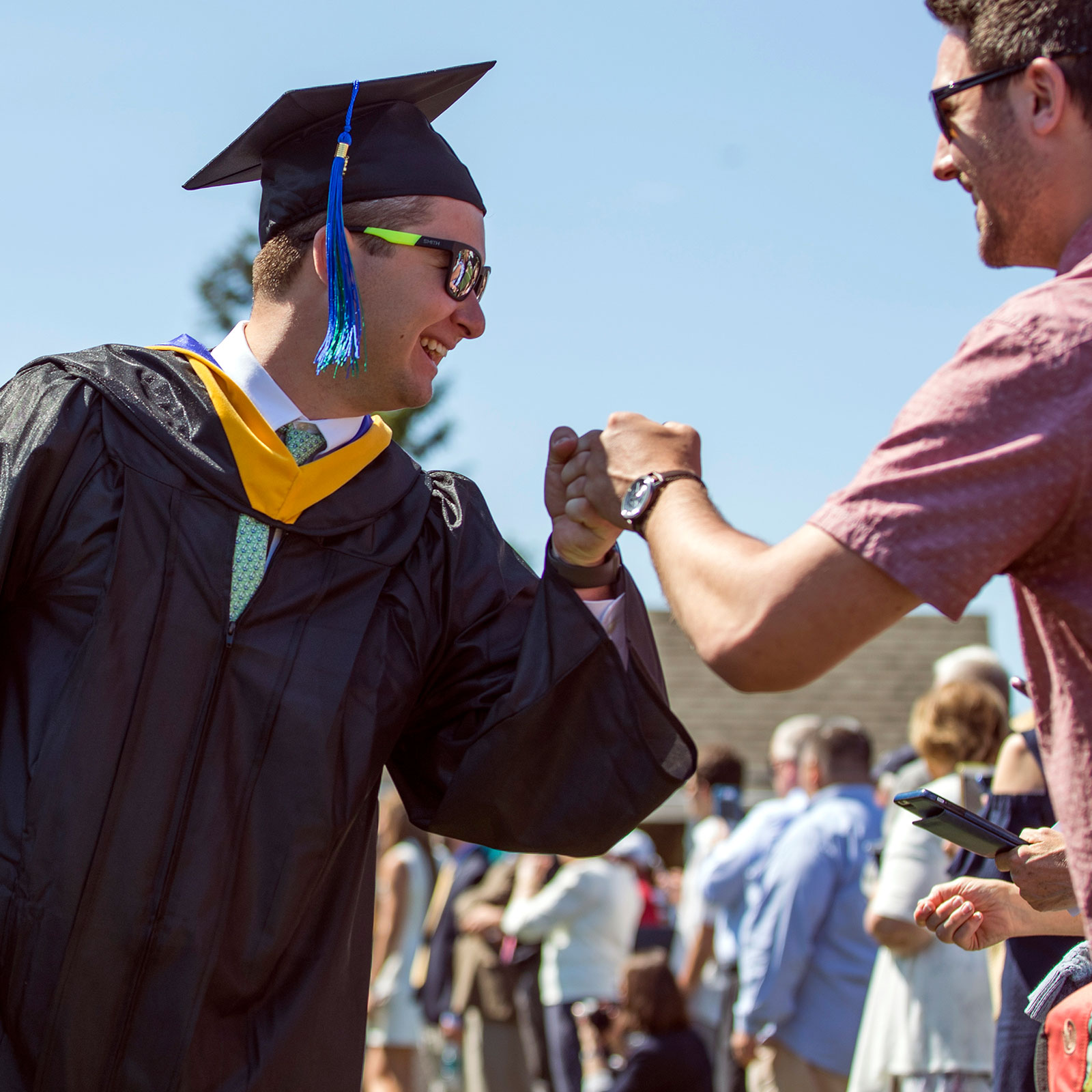 Graduate giving a fist bump to family member