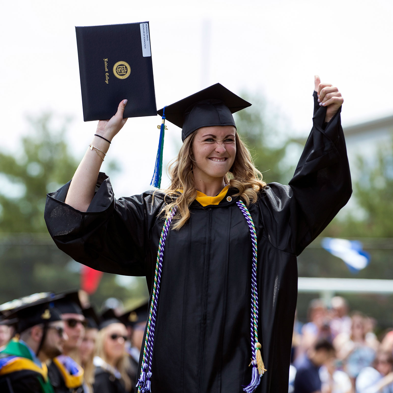Graduate holding up diploma