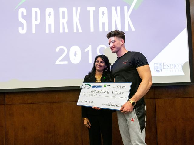 Winner of 2019 Spark Tank stands with check.