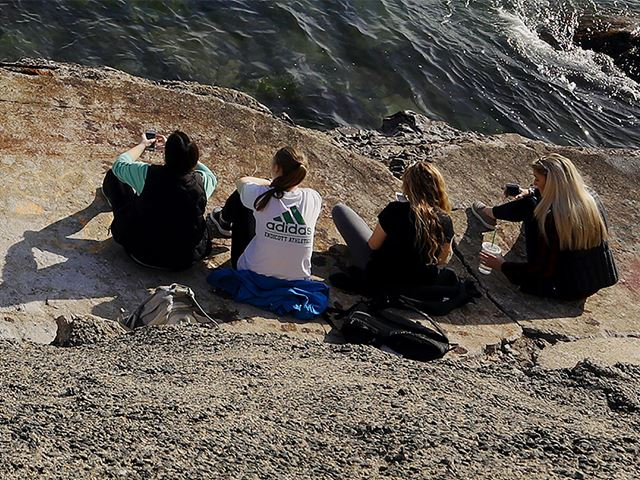 Four students sitting at Peace Rock next to the Atlantic ocean