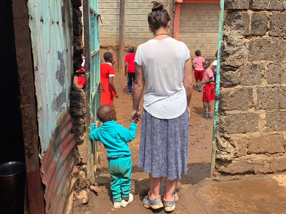 Emma Roca '21 holding a young child's hand at an orphanage in Africa
