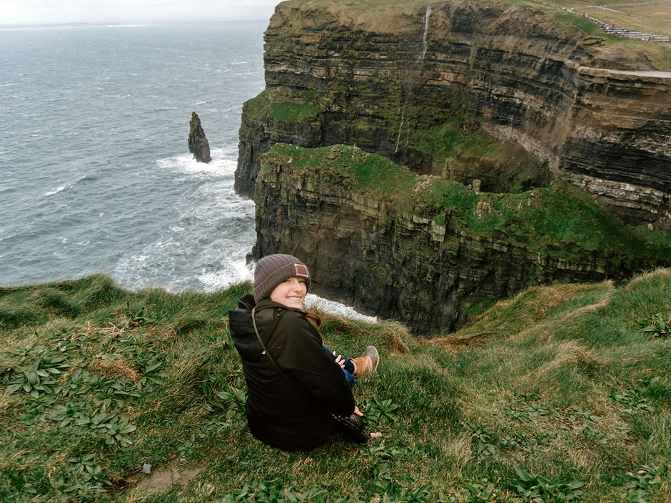 Female student sitting on the Cliffs of Moher smiling back at the camera
