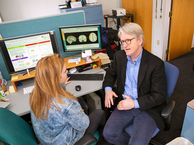 Distinguished Faculty Dr. John Kelly and Kylie Isenburg '16 collaborating on research