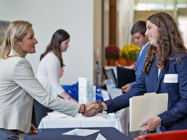 Lindsay Campbell (right) shaking hands with a recruiter at Meet the Firms