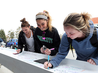 Students signing a beam that was placed in Phase I of the Wax Academic Center