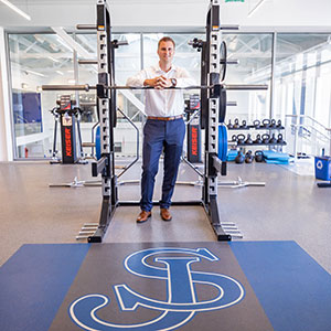Jameson Pelkey leaning over a squat rack inside the St. John's Prep Wellness Center