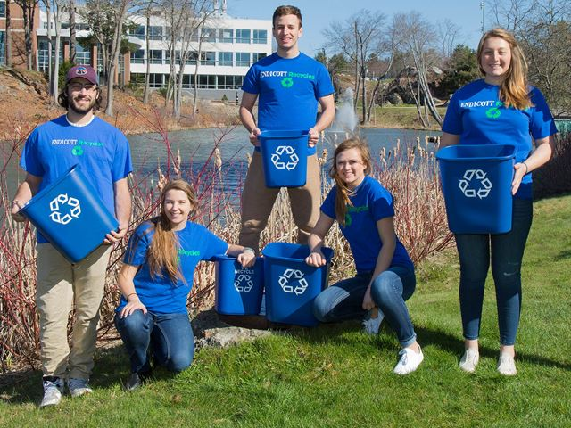 Students hold recycling bins outside a pond at Endicott College