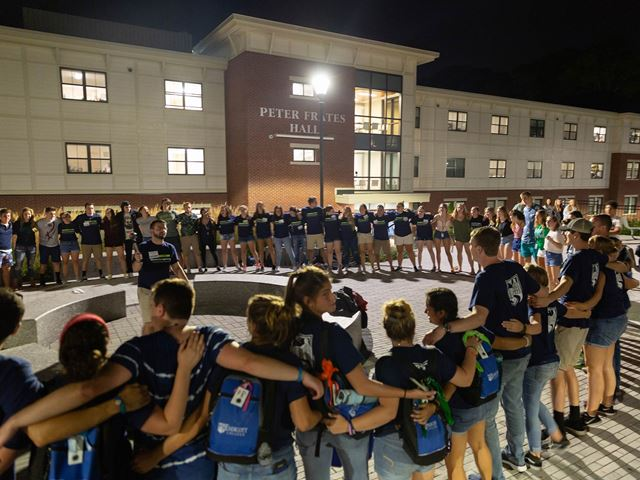 Students in a circle during orientation in front of Frates Hall during Fall orientation.