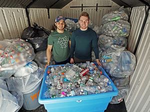 Two Endicott students standing behind a large container filled with cans to be recycled