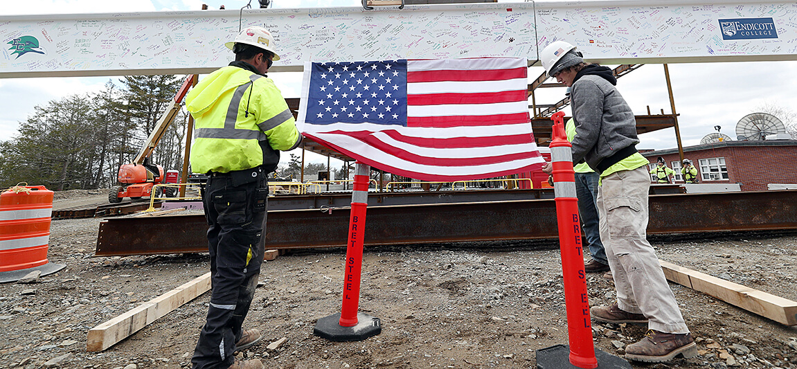 New Academic Center topping off ceremony two workers ready beam for uploading