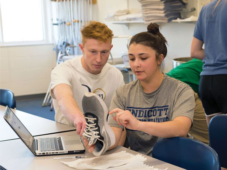 Athletic trainers holding a shoe