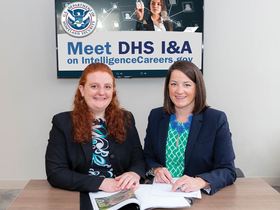 Endicott's Jaclyn Flaherty and Engrid Backstrom sitting in front of DHS sign