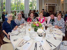 Alumni gathered around a table at Tupper Manor
