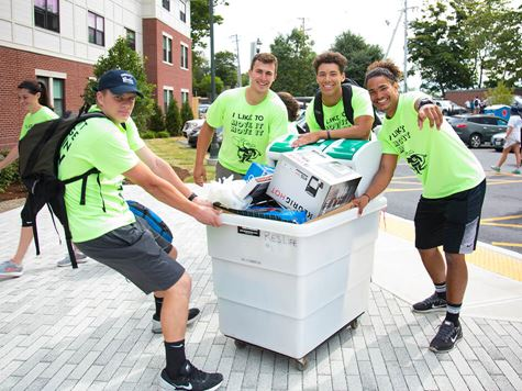 group of guys pulling/pushing cart full of belongings on move in day