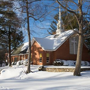 winter shot of on campus chapel from a distance through the trees