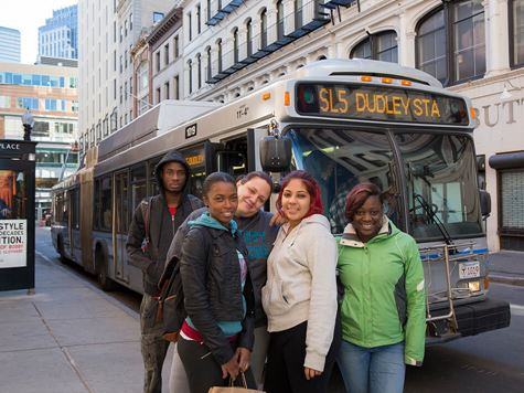 students in boston in front of city bus