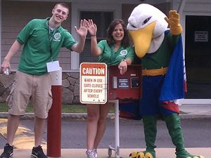 two people standing with endicott gull mascot outside of campus safety building