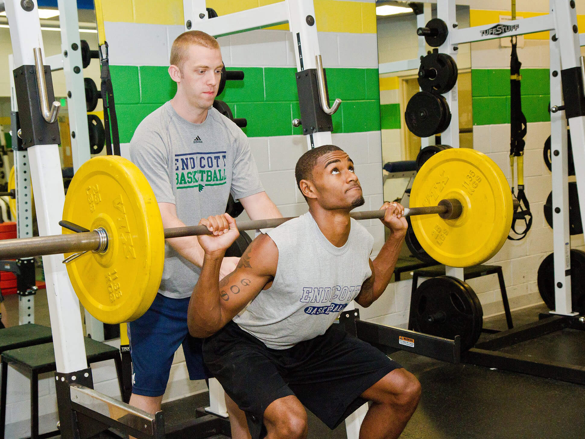 student lifting weights in fitness center with friend spotting his lifting