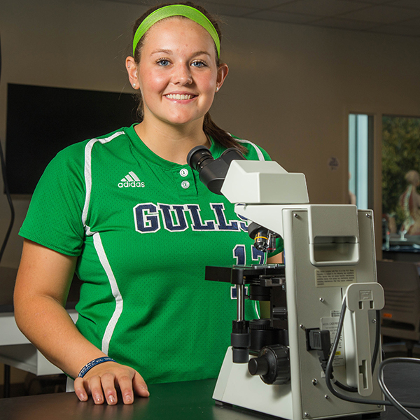 student athlete working with microscope in a lab