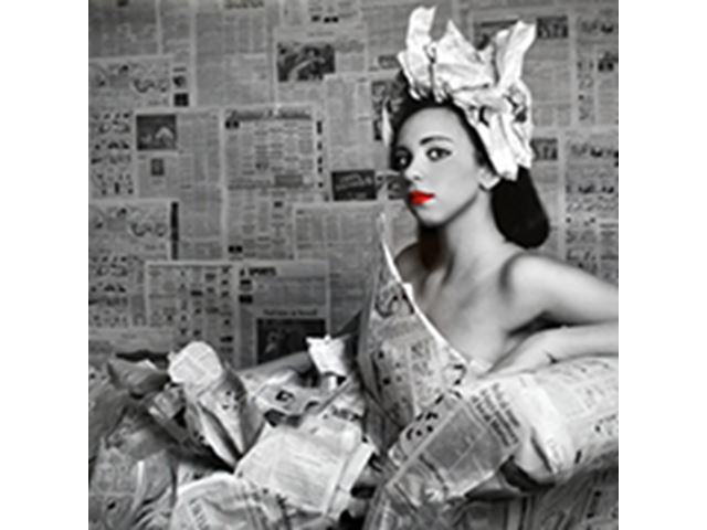 a woman sitting in a dressed made from newspapers