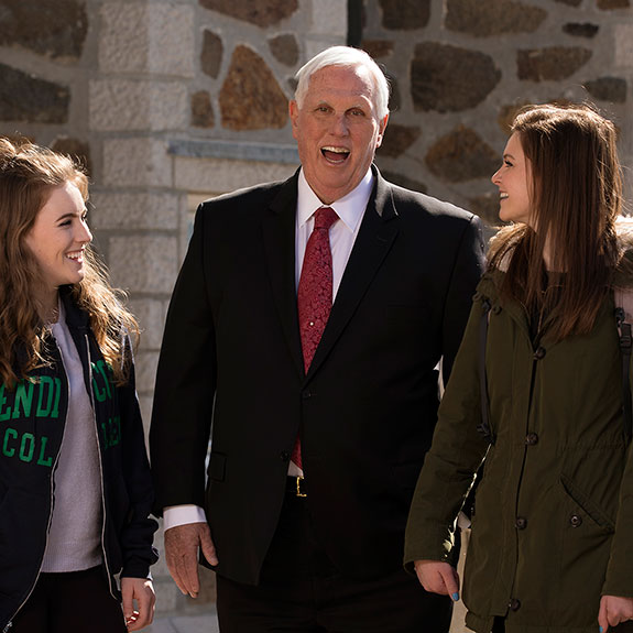 the president of the college laughing and talking with two students