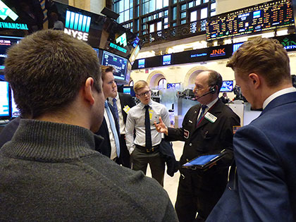 a man talking to a group of business professionals in the stock market exchange