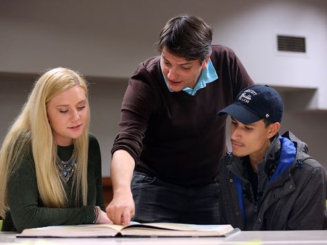 a student success faculty member helping two students
